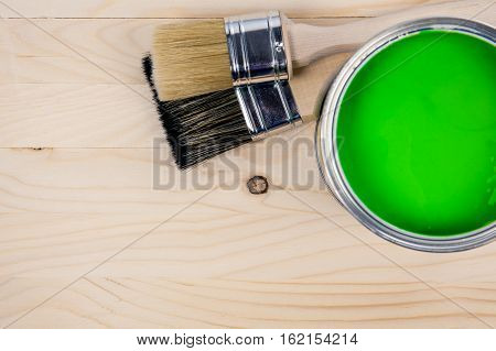 Colorful bucket of green paint with two brushes on a wooden table