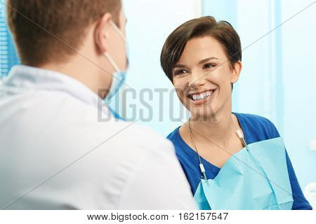 Young female patient visiting dentist office. Beautiful smiling woman with healthy straight white teeth sitting at dental chair.Dental clinic.Stomatology
