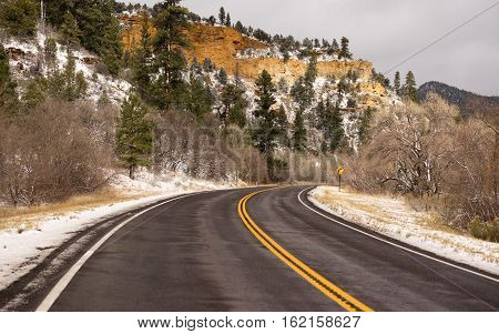 The road curves in front of Red Rock Bluffs on Utah 89