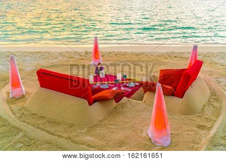 Dining table on beach at tropical Maldives island .
