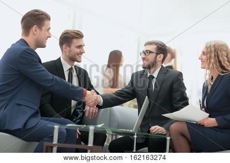 Congratulations! Two cheerful businessmen shaking hands while be