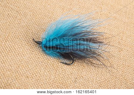 Closeup of Colorful Fishing Fly on Burlap Background