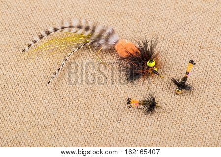 Close Up of Colorful Fishing Flies on Burlap Background