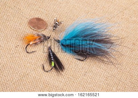Arrangement of Fishing Flies of Various Sizes on Burlap Background