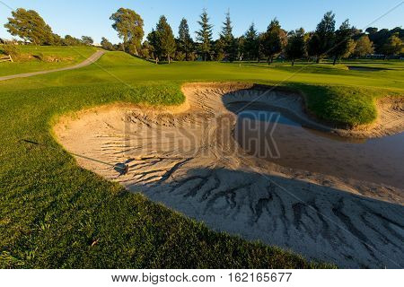 A bunker is half full of water after a storm next to a green