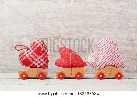 Valentine's day concept with toy car and heart shape over rustic background