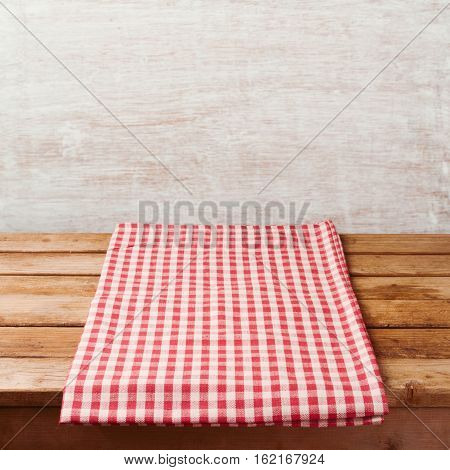 Empty wooden deck table with checked tablecloth over rustic wall. Background for product montage display