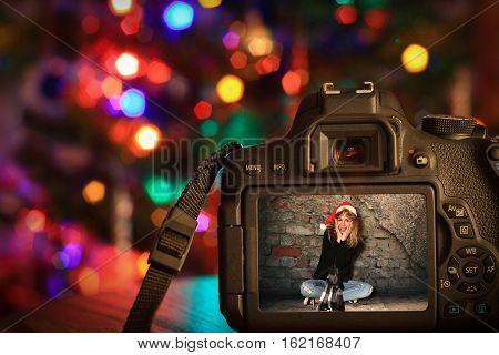 Christmas scene of a digital camera Infront of a Christmas tree.