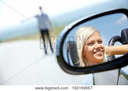 Female face in a rear-view mirror in car