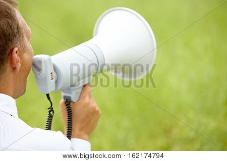 Rear view of a man with loud speaker