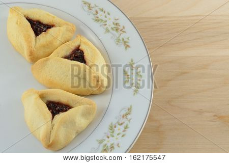 Hamantaschen raspberry pastries on white plate n wooden table