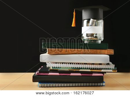 School supplies and glass jar with money for education on wooden table against dark background