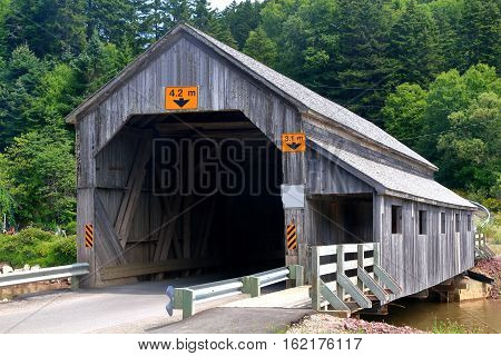 Covered wooden bridge Irish River Number 2 in St. Martins New Brunswick still in use visible is pedestrian section of the bridge built in 1946