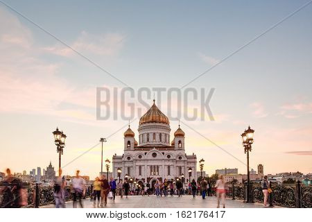 Pedestrian Patriarchal bridge with people on it on the background of the Orthodox Cathedral of Christ the Savior
