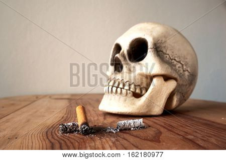 Close up of cigarette stub and blured human skull