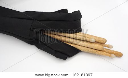 Drum sticks and black bags on white background.
