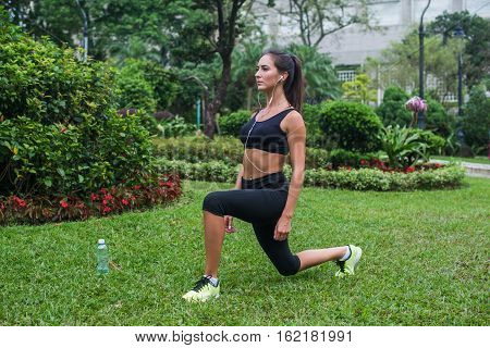 Slim athletic woman working out in park doing knee-bounce exercise or lunges