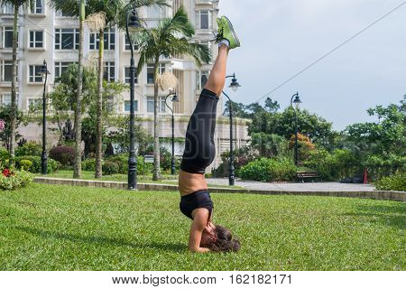 Beautiful slim sporty young woman doing handstand or supported headstand exercise outdoors. Fitness girl practicing yoga posture in park.