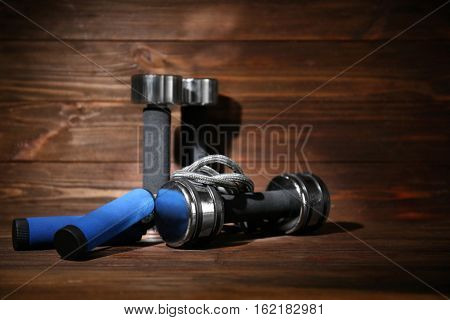 Dumbbells and skipping rope on wooden background
