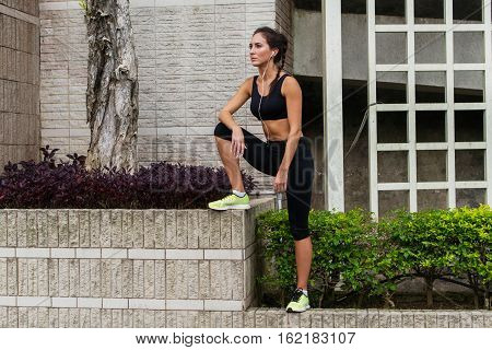Fitness girl recovering after jogging or exercising outside in urban area, listening to music in earphones and looking into the distance.