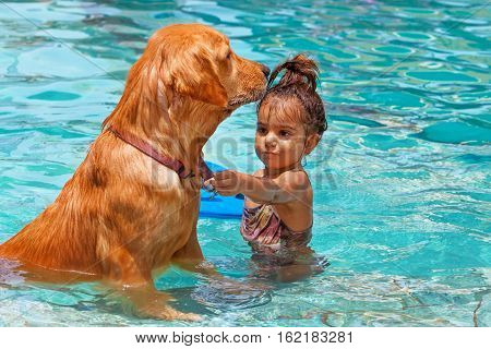 Funny photo of little baby swimming in outdoor pool playing with retriever puppy. Children water sports activity and swimming lessons training dogs fun games with family pet on summer vacation.