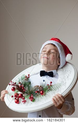 proud boy in Santa's hat and bow tie with a Christmas wreath on his neck