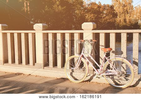 Bicycle parked near bridge banisters