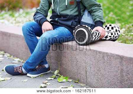 Teenager sitting on parapet with gyroscooter in autumn day, close up