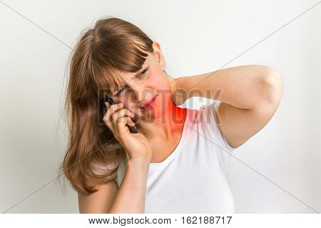 Woman With Mobile Phone Having Pain In Her Neck