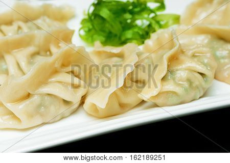 Asian dumplings with sauce and greens in Korean style