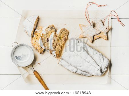 Traditional German Christmas cake Stollen cut in pieces with festive gingerbread star shaped cookies on white background, top view, horizontal composition