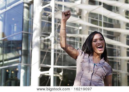 Woman recieving good news raises her arm in triumph.
