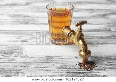 Water shortage concept. Glass of dirty water and tap on wooden background