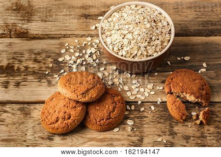 Oatmeal cookies and bowl with groats on wooden background