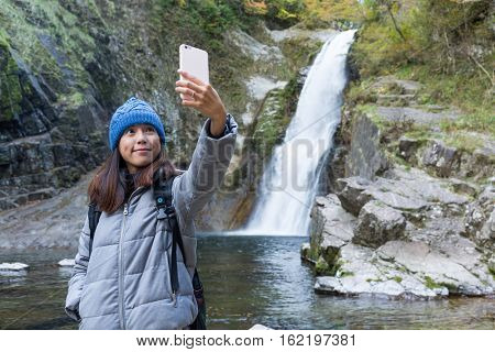 Woman taking selfie in forest with waterfalls