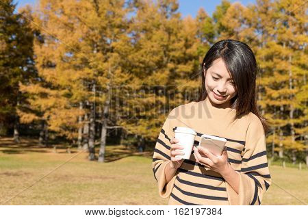 Woman using cellphone and carry with coffee at outdoor in Autumn season