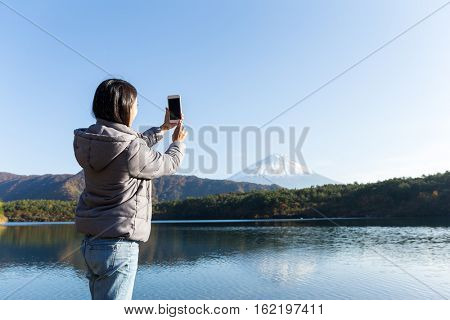 Woman take photo on cellphone on Fujisan