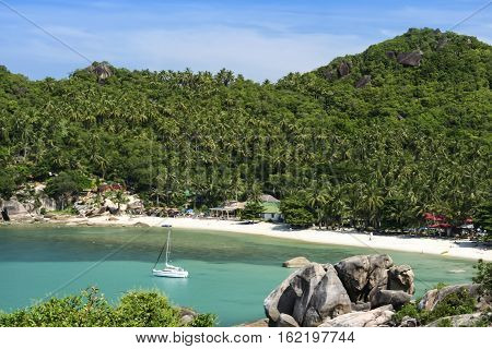 white sailboat anchred in beautiful crystal bay surrounded by jugle clad hills near lamai on ko samui island in the gulf of thailand