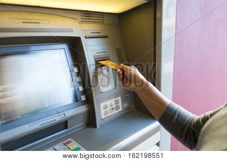 finance, money, bank and people concept - close up of woman hand inserting card to atm machine