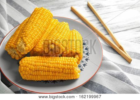 Plate with tasty boiled corncobs and wooden tongs on kitchen table, close up view