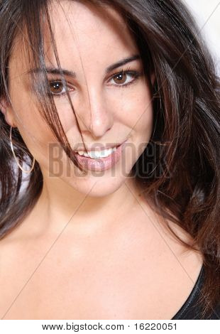 Portrait of an attractive young woman smiling with long flowing brown hair.
