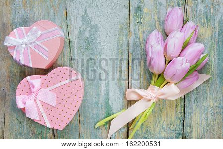 Bouquet of pink tulips tied with a satin ribbon and two gift boxes in the shape of a heart with a bow on the old blue wooden background with space for text
