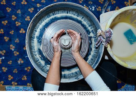 Woman's hands. Potter at work. Creating dishes. Potter's wheel. Dirty hands in the clay and the potter's wheel with the product. Creation. Working potter.