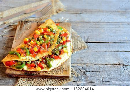 Roasted vegetable stuffed omelette on old wooden background with copy space for text. Spicy omelette stuffed with red and green bell peppers and canned corn. Fork, knife, burlap textiles on table