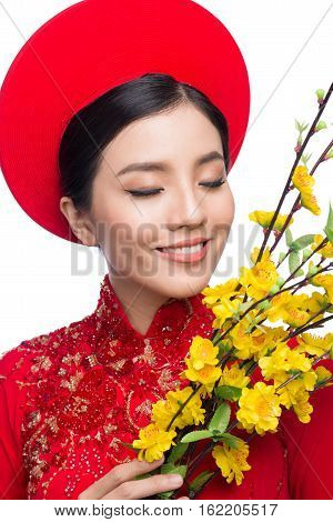 Portrait Of A Beautiful Asian Woman On Traditional Festival Costume Ao Dai Holding Hoa Mai Tree (och