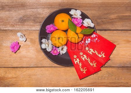 """Mandarin Oranges And Lunar New Year With Text """"happy New Year"""" On Red Pocket. Tet Holiday Concept."""