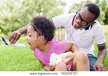 African American Daughter Playing Airplane Toy With Father In Outdoor Green Park