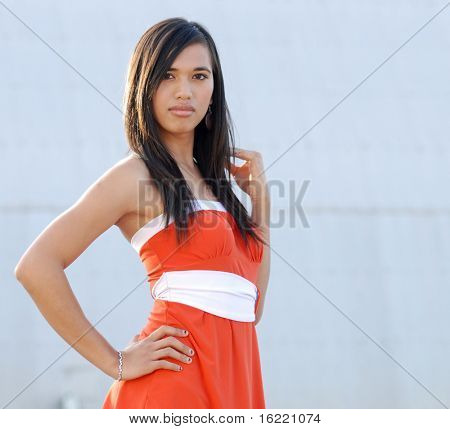 Attractive young woman swearing orange dress in fashion pose with copy space to right