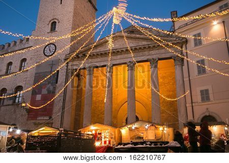 ASSISI, ITALY. DECEMBER 16, 2016. View of Minerva's temple in Assisi with christmas market, decorations and lights at twilight