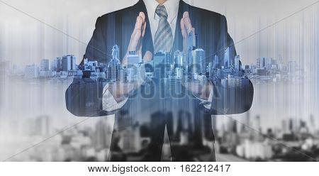 Double exposure businessman holding blue city hologram, real estate business technology